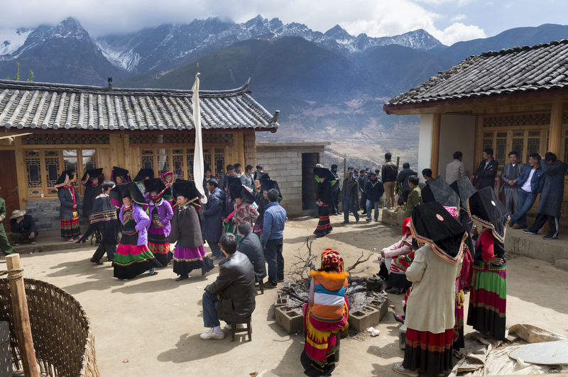 The courtyard house of the deceased's family in Snowflake village. As each group of guests arrives from their own village, they are led in by the Lala, who carries white cloth on a pole. Yulong Snow Mountain behind.