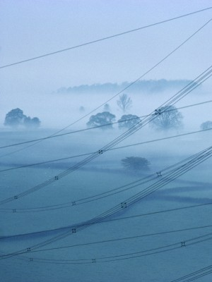 Power lines and pylons crossing misty valley, Gloucestershire, West of England